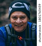 Small photo of White adult man in the outdoors on a green background. Hispanic hiker smiling to the camera with black eyes wearing a black bennie in the forest.