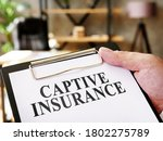 Small photo of Hand holds documents Captive insurance about insurance.