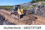A Bulldozer Spreads Out A Pile...