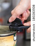 Small photo of Man opening a tin of canned food using a manual can-opener attached to the rim on the lid as he penetrates the metal to break the airtight seal
