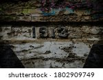 A closeup shot 1913 curved on an old weathered wall