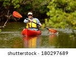 Man Paddling In A Red Kayak In...