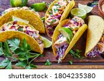 Small photo of salmon tacos with red cabbage salad with spicy yogurt sauce sprinkled with finely chopped parsley served on a rude cutting board on a dark wooden table, horizontal view from above, close-up