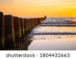 Wooden Poles At The Beach At...