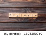 Small photo of EVALUATE word written on wood block. EVALUATE text on cement table for your desing, concept.