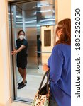 Small photo of Woman with face mask and visor waiting for elevator while a young adult holds the door for her