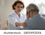Small photo of Caring young woman doctor comforting depressed unhealthy mature patient at meeting in hospital, therapist physician gp caregiver touching senior man shoulder, expressing empathy and support