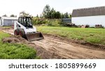 A Skid Steer Loader Clears The...