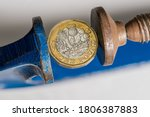 Small photo of Concept for financial stress or recession with UK one pound sterling coin being squeezed between the jaws of a large vise. Detailed macro shot of vice