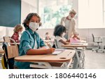 Small photo of Multiracial pupils of primary school are ready to study after Covid-19 quarantine and lockdown. Children in class room with teacher wearing face masks and using antiseptic for coronavirus prevention.