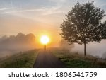 Small photo of Sunrise fog silhouette of a cyclist. Ealy morning mist trip. Early morning sunrise travel. Sunrise in early morning