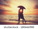 Couple Kissing Under Umbrella...
