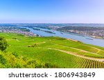 Aerial panoramic view of river Rhine Gorge or Upper Middle Rhine Valley winemaking region with vineyards green fields, Rudesheim am Rhein town, blue sky, Rhineland-Palatinate, Hesse states, Germany