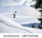 Side view snapshot of skier conducting extreme jump from a snowy slope, flying against amazing sky and mountain range on background. Copy space. Concept of skiing and winter sport activities.