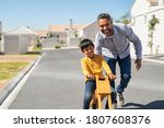 Small photo of Happy latin father helping smiling boy to ride wooden balance cycle on street. Happy middle eastern child and young dad riding bike. Smiling daddy teaching son to ride a balance bicycle, copy space.