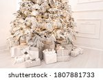 Christmas presents under New Year tree with artificial snow with golden illumination. Silver color.