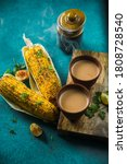 Small photo of Top view of brewed hot milk tea with roasted grilled corn on blue background. Delicious Grilled Corncobs and Two Cups of Chai, an ideal Indian monsoon brunch good for boosting immunity and health.
