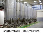 Small photo of Stainless vertical steel tanks with pressure meter in equipment tank chemical cellar at the with scrolling wheel stainless steel tanks cleaning and treatment at shampoo plant