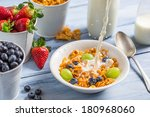 Cornflakes with fruits flooded with milk - stock photo