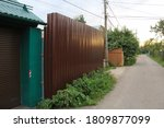 Small photo of striped shadow from fence in village. Wooden fence. Separate and protect private property. Outside built new wooden fence construction surrounding dutch garden. Aluminum Fence With Decorative Elements