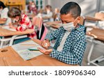 Small photo of Multiracial pupils of primary school are ready to study after Covid-19 quarantine and lockdown. Children in class room wearing face masks and using antiseptic for coronavirus prevention.