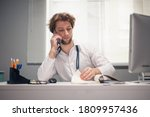 Male doctor talking on the phone, while using his computer, looking at the monitor in his office. - stock photo