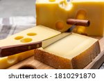Swiss cheeses, block of medium-hard yellow cheese emmental or emmentaler with round holes and matured gruyere close up