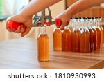 Small photo of Man using hand capper for brewing, with brown bottles of homemade liquor or alcohol. Selective focus.