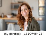 Small photo of Portrait of smiling mature woman looking at camera with big grin. Successful middle aged woman at home smiling. Beautiful mid adult lady with long red hair enjoying whitening teeth treatment.