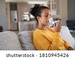 Small photo of Black woman holding a mask nebulizer inhaling fumes medication into lungs. African sick lady inhaling through inhaler mask at home. Self treatment of the respiratory tract using inhalation nebulizer.