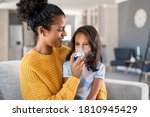 Small photo of Little indian girl making inhalation with nebulizer with lovely mother. Woman makes inhalation to a sick child while embracing her. Mom helping daughter with cold and flu to inahale nebuliser aerosol.