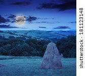 a pair of haystacks and a tree on a green meadow at the foot of the mountain at night in moonlight - stock photo