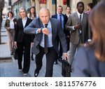 Small photo of Stressed businessman is late for meeting, checking time hastily on his watch and running on city street..