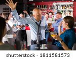 Small photo of Tipsy businessman with young female colleague fooling during office party at nightclub