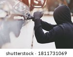 Small photo of Close up car thief hand holding screwdriver tamper yank and glove black stealing automobile trying door handle to see if vehicle is unlocked trying to break into inside.