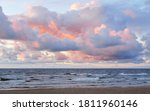 Small photo of Clear sky with lots of glowing colorful pink cumulus clouds above the Baltic sea shore after thunderstorm at sunset. Dramatic cloudscape. Warm golden sunlight. Picturesque scenery. Fickle weather