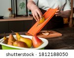 Small photo of Close-up of unrecognizable woman standing at kitchen counter and slicing pear on mandoline