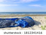 Disassembled Blue Tent On Sand...