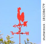 Small photo of A bright red weathercock isolated against a blue sky