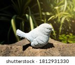 A Grey Stone Bird Sitting On A...