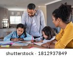 Small photo of Indian parents helping children with their homework at home. Middle eastern father and african mother helping daughters studying at home. Little girls completing their exercises with the help of dad.
