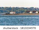 USA, Washington State, Seattle. West Point Lighthouse (northern point of Elliott Bay) and keeper cottages. Masts of sailboats Shilshole Marina behind