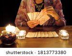 Small photo of Tarot reading or fortune teller holding and picking tarot cards in her hands with burning candles and tarot cards spreading on a wooden table.Divination or forecasting concept.