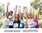 Small photo of Group of marathon runners cheering after winning a race in the park