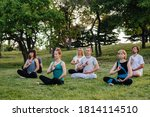 A Group Of People Do Yoga In...