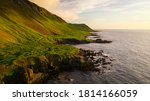 Icelandic nature landscape if the cliffs covered in green grass and moss and atlantic ocean on the other side in golden hour