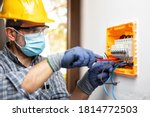 Small photo of Electrician at work on an electrical panel protected by helmet, safety goggles and gloves; wear the surgical mask to prevent the spread of Coronavirus. Construction industry. Covid 19 Prevention.