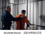 Small photo of The prison warden puts the prisoner behind bars after the court verdict and locks the cell