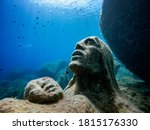 """Small photo of Close up of the statue of """" Madonna del Naufrago """" under the water in the protect area of Capo Carbonara in Villasimius. Madonna with child statue underwater. Madonna of castaway."""