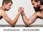 Small photo of Two man's hands clasped arm wrestling, strong and weak, unequal match. Heavily muscled bearded man arm wrestling a puny weak man. Arms wrestling thin hand, big strong arm in studio.